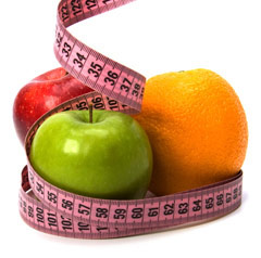Apples and Orange surrounded by tape measure